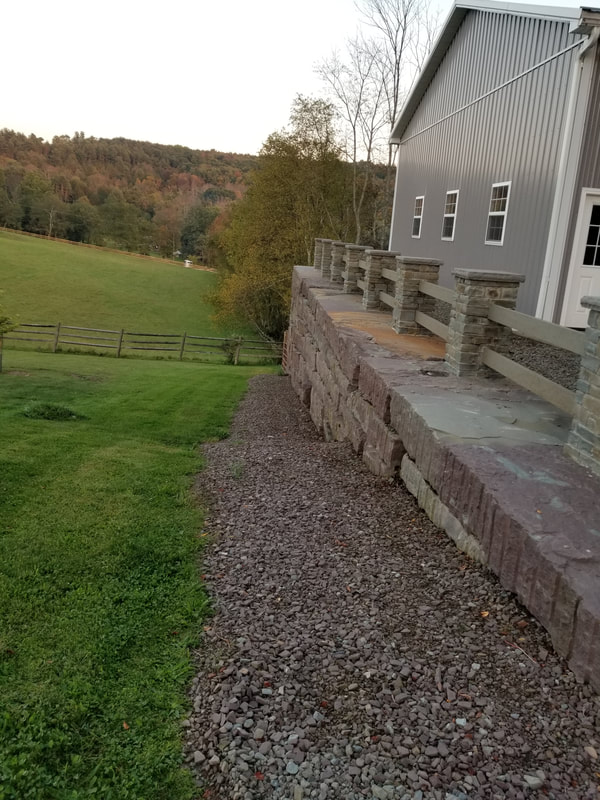 Large retaining wall made with large cubes, the pillars are finished with our thin veneer and pier caps. The railing is also custom made from our stone.